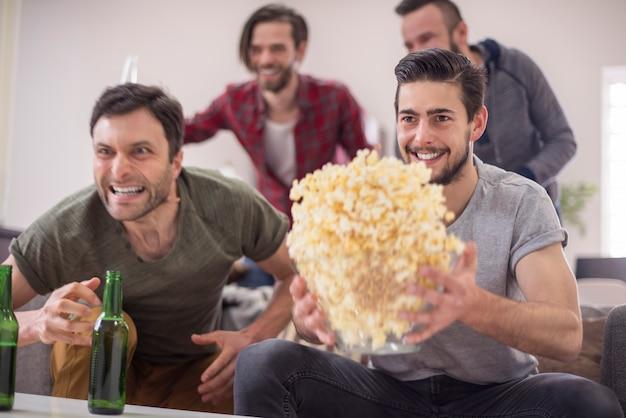 Freunde trinken bier und schauen fußballspiel Kostenlose Fotos