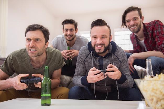Freunde trinken bier und spielen videospiele