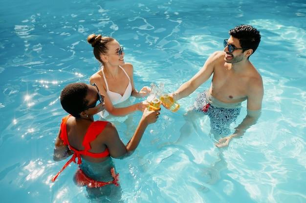 Freunde trinken getränke im pool, ansicht von oben. fröhliche leute, die spaß in den sommerferien haben, urlaubsparty am pool im freien
