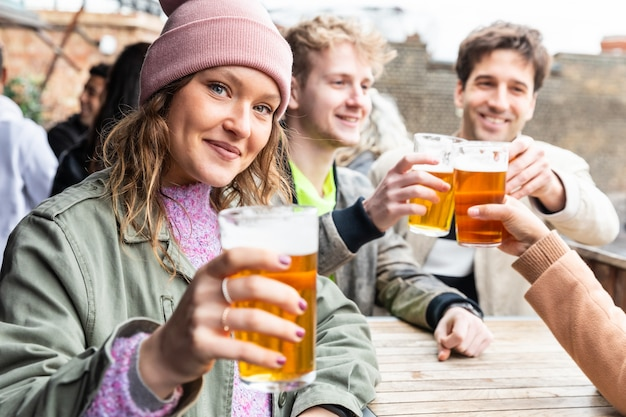 Freunde trinken und rösten mit bier in der kneipe