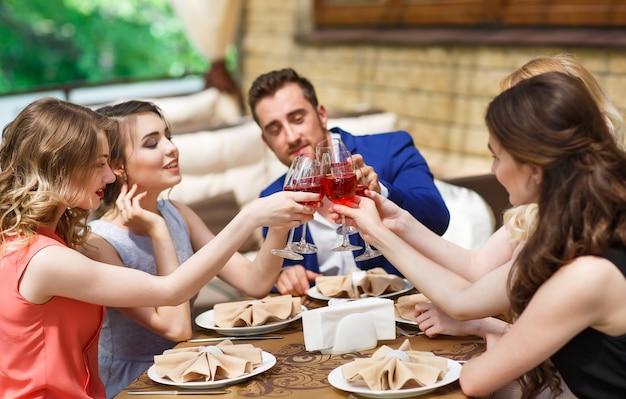 Freunde trinken wein auf der sommerterrasse.