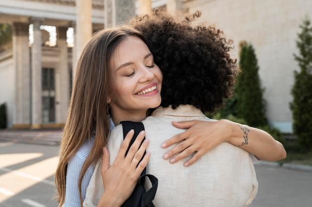 Freunde umarmen sich, nachdem sie sich im freien gesehen haben