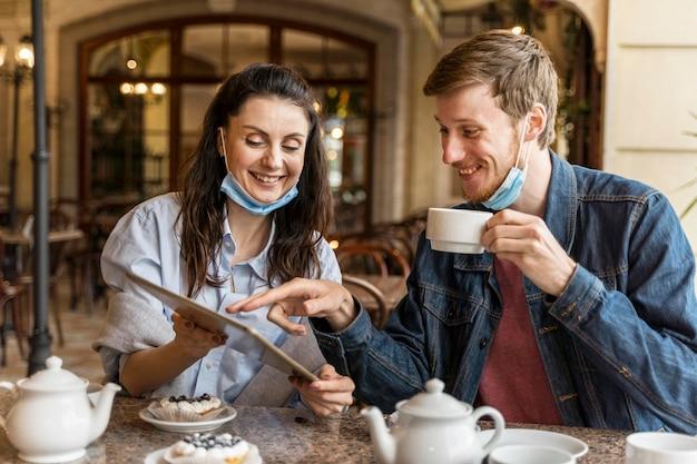Freunde unterhalten sich im restaurant, während sie medizinische masken am kinn haben