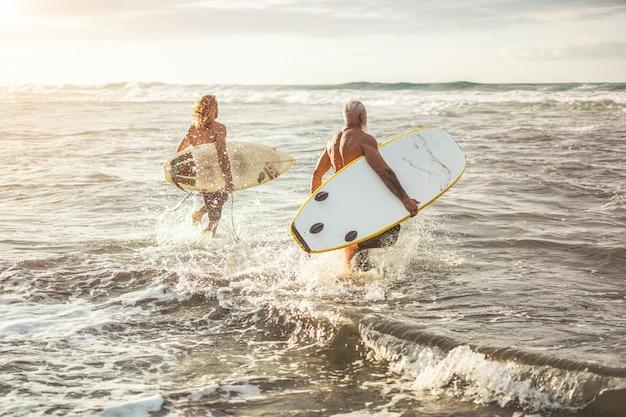 Freunde unterschiedlichen alters, die bei sonnenuntergang am strand zum surftraining laufen