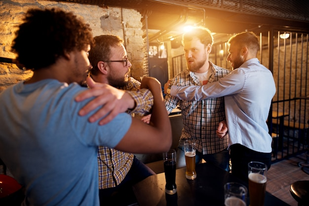 Freunde verhindern den kampf zweier wütender männer in der bar.