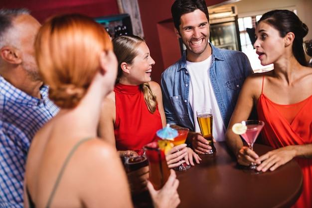 Freunde, welche bei tisch die getränke im nachtklub genießen