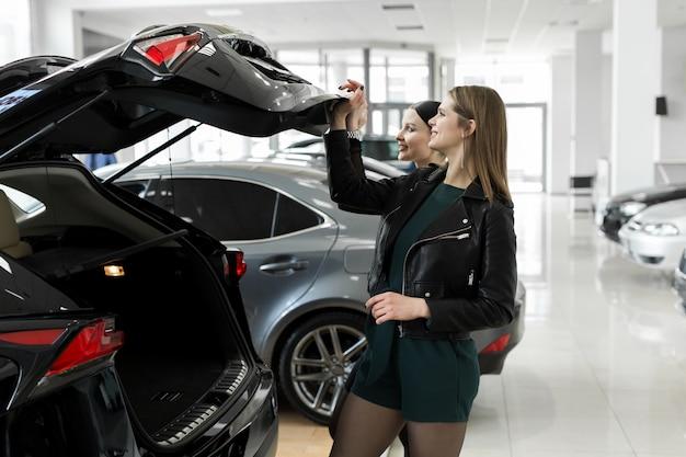 Freunde zwei frauen wählen ein auto in einem autohaus und überprüfen den kofferraum.