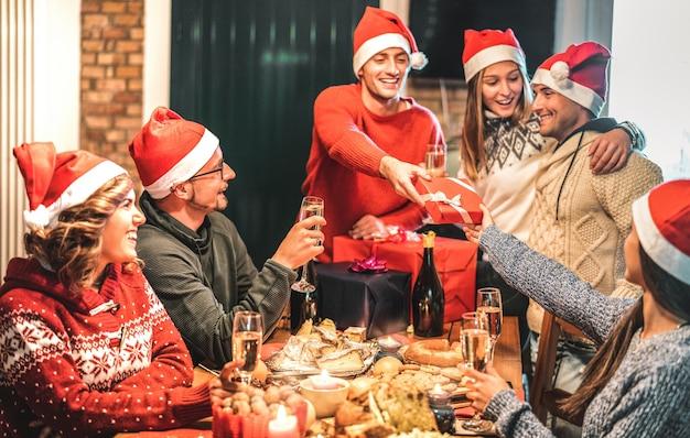 Freundesgruppe trägt weihnachtsmütze und gibt sich gegenseitig weihnachtsgeschenke
