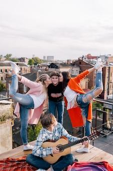 Freundesparty auf dem dach. fröhliche freizeit. sport und musik für junge leute, lustiger zeitvertreib im freien