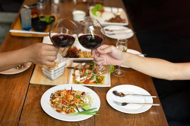 Freundfeiermittagessen mit den händen, die glasrotwein mit lebensmittel rösten.