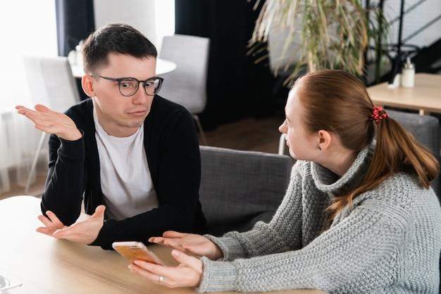 Freundin bittet um erklärung ihres freundes, der auf einer couch im café sitzt