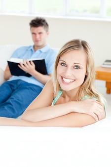 Freundin, die an der kamera lächelt, während ihr freund ein buch auf dem sofa liest