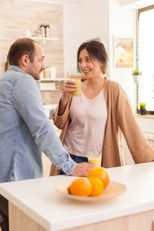 Freundin, die nahrhaften smoothie hält, während sie ehemann in der küche anlächelt. gesunder, unbeschwerter und fröhlicher lebensstil, ernährung und frühstückszubereitung am gemütlichen sonnigen morgen