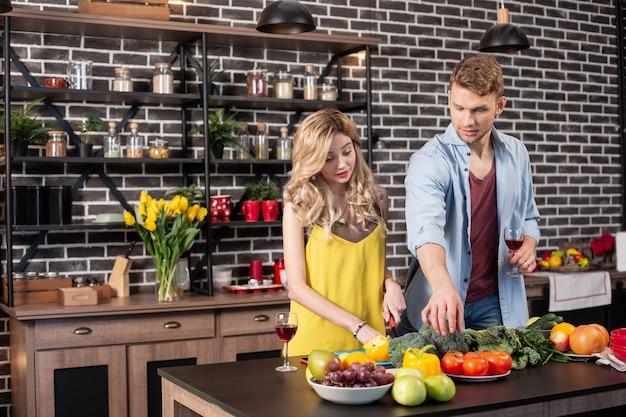 Freundin helfen. fürsorglicher liebevoller mann mit jeanshemd, der seiner freundin beim kochen des abendessens in der küche hilft