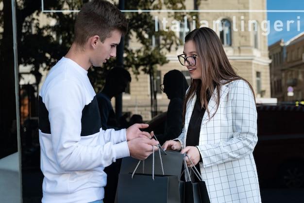 Freundin ist überrascht und erfreut über die einkäufe ihres freundes. glücklicher blick der jungen frau in eine einkaufstasche.