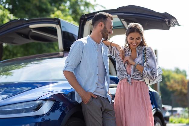 Freundin lächelt. liebevolle freundin, die lächelt, während sie mit ihrem freund in der nähe eines luxusautos spricht?