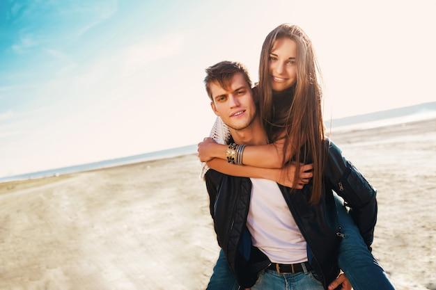 Freundin und freund umarmen sich glücklich. junges hübsches verliebtes paar, das auf dem sonnigen frühling entlang des strandes datiert. warme farben.