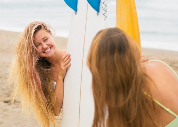 Freundinnen am strand, die spaß mit surfbrett haben