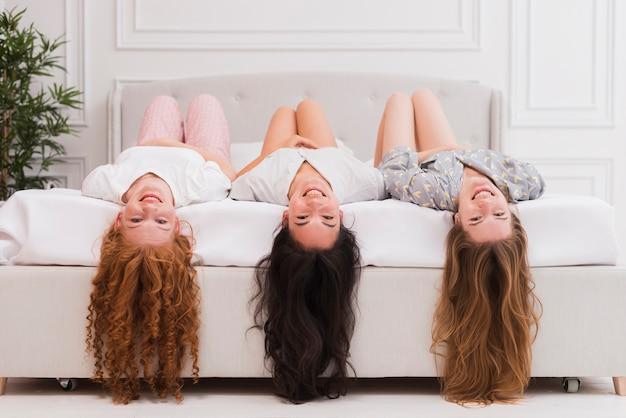 Freundinnen auf der pyjama-party, die mit dem kopf nach unten hängt