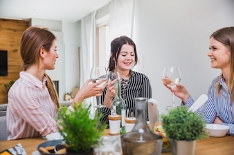 Freundinnen, die am Tisch feiern sitzen