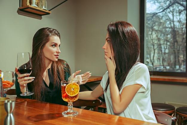 Freundinnen, die an der bar etwas trinken. sie sitzen an einem holztisch mit cocktails. sie tragen freizeitkleidung.
