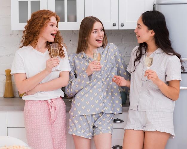 Freundinnen, die an der pyjama-party etwas trinken