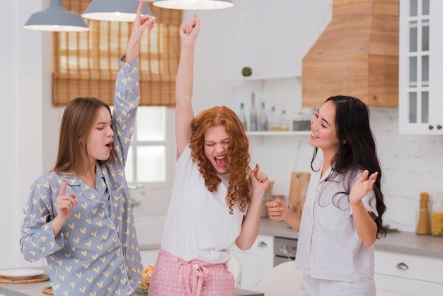Freundinnen, die an der pyjama-party tanzen