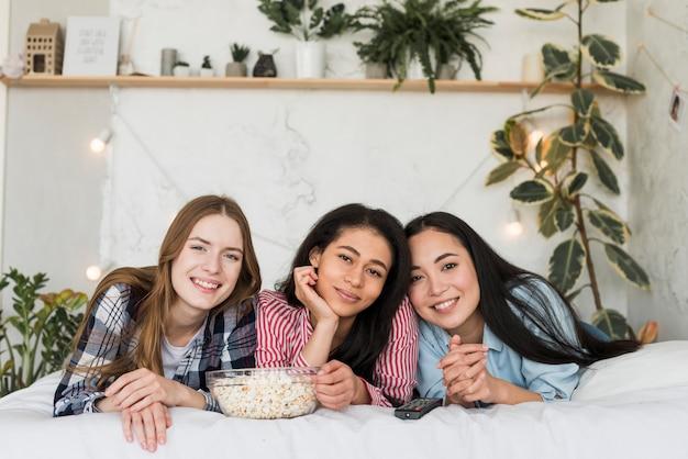 Freundinnen, die auf bett sich entspannen
