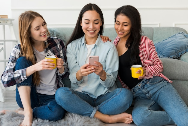 Freundinnen, die auf dem boden betrachtet smartphone sitzen
