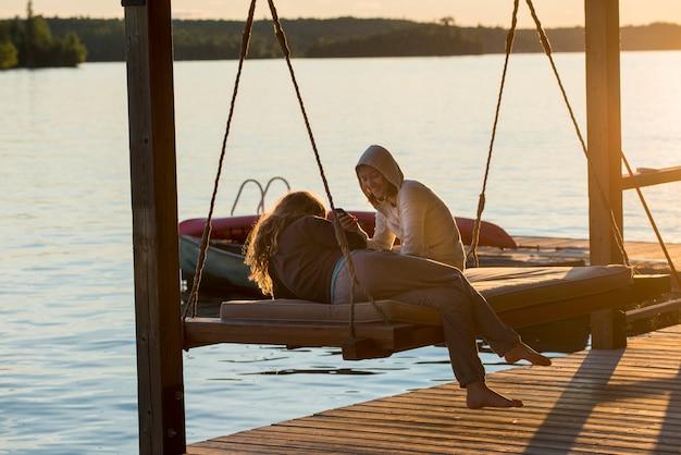 Freundinnen, die auf schwingstuhl am dock, see des holzes, ontario, kanada genießen
