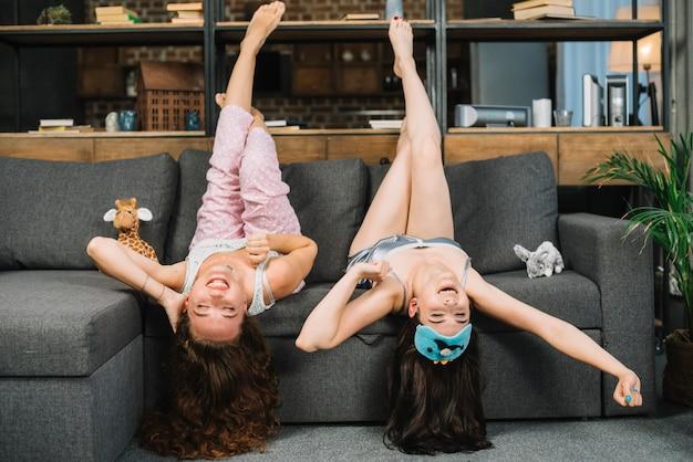 Freundinnen, die auf sofa umgedreht sich hinlegen