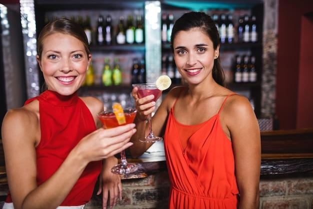 Freundinnen, die cocktail am zähler im nachtklub genießen