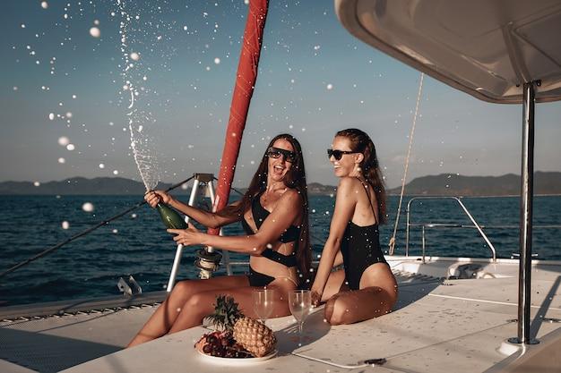 Freundinnen, die den feiertag feiern, indem sie champagner öffnen. zwei mädchen haben spaß auf ihrer riesigen weißen yacht.