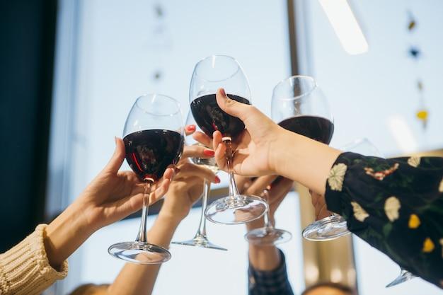 Freundinnen, die eine party haben und gläser rotwein halten