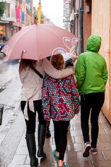 Freundinnen, die einen regenschirm im regen auf einer straße, uppsala, schweden halten