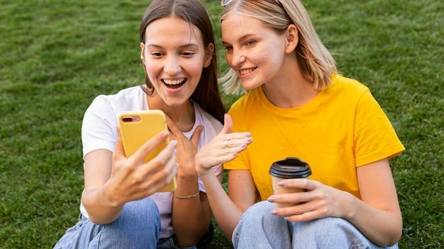 Freundinnen, die gebärdensprache verwenden, um am telefon zu sprechen