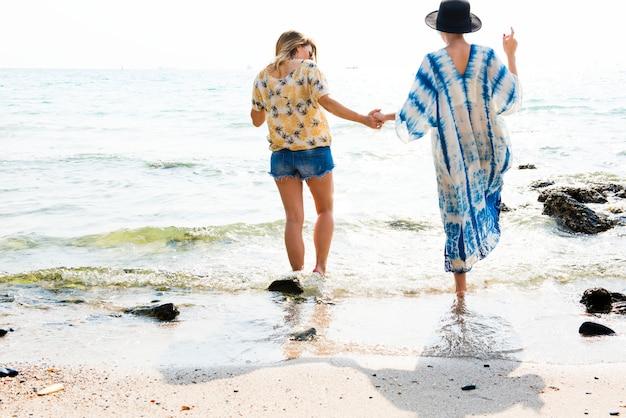 Freundinnen, die hände halten und auf den strand gehen