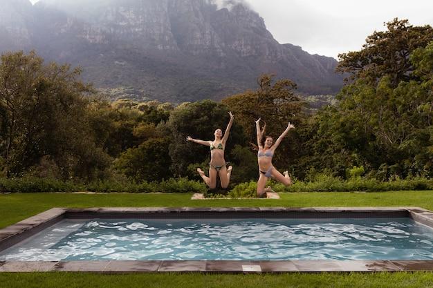 Freundinnen, die in swimmingpool am hinterhof springen