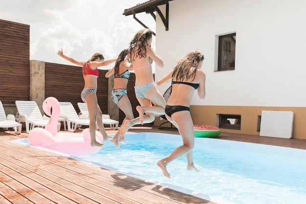 Freundinnen, die in swimmingpool springen