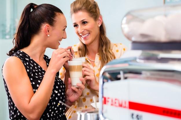 Freundinnen, die latte macchiato im café trinken