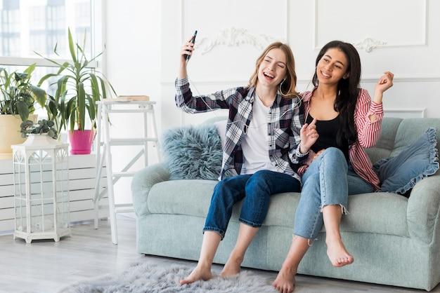 Freundinnen, die musik mit den kopfhörern sitzen auf couch hören