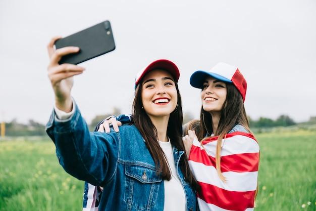 Freundinnen, die selfie auf dem gebiet machen