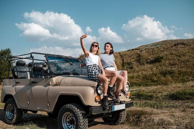 Freundinnen, die selfie nehmen, während sie mit dem auto reisen
