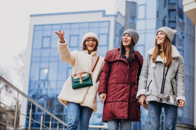 Freundinnen, die sich zusammen zur winterzeit außerhalb der straße treffen