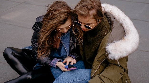 Freundinnen, die spaß zusammen im freien mit smartphone haben