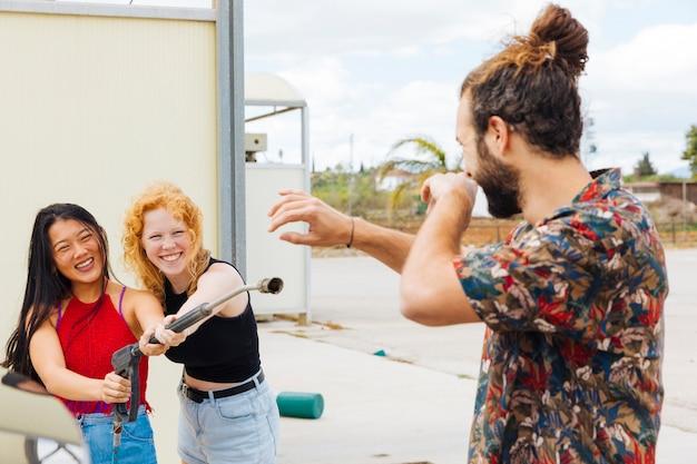 Freundinnen, die wasser auf schützendem mann an der waschanlage spritzen