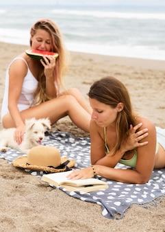 Freundinnen, die wassermelone am strand mit hund essen