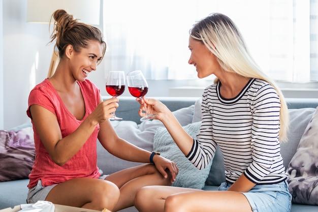Freundinnen, die zu hause pizza mit wein auf sofa essen