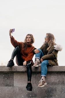 Freundinnen, die zusammen selfie draußen nehmen