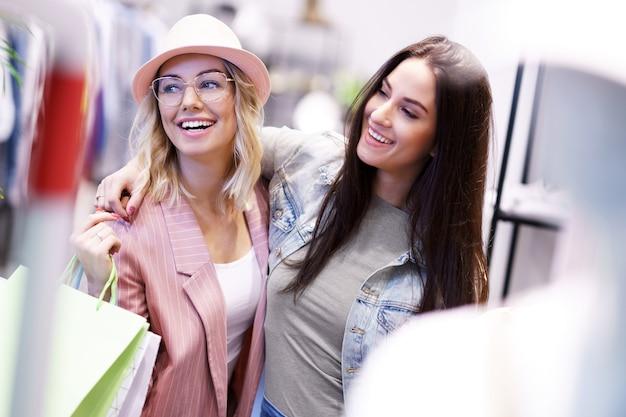 Freundinnen einkaufen für kleidung im laden shopping